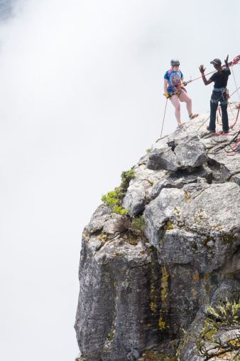 Cape Town, South Africa - March 16, 2013: Female tourist  leans back on a rope as she stands on a cliff preparing to rappel, or abseil, down the rock face as her guide gives her instructions with outstretched hands at Table Mountain National Park