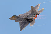 F-22 Raptor in a  high G maneuver, with condensation trails forming  at the wings tip and afterburners on