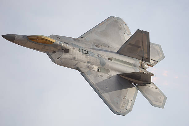 F-22 Raptor in a turn, with afterburner on F-22 Raptor in a turn, with afterburner on supersonic airplane stock pictures, royalty-free photos & images