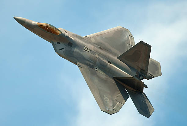 F22 Raptor jet flying in clear blue sky A F22 Raptor stealth fighter in flightTo see my other aviation images please click the image below supersonic airplane stock pictures, royalty-free photos & images