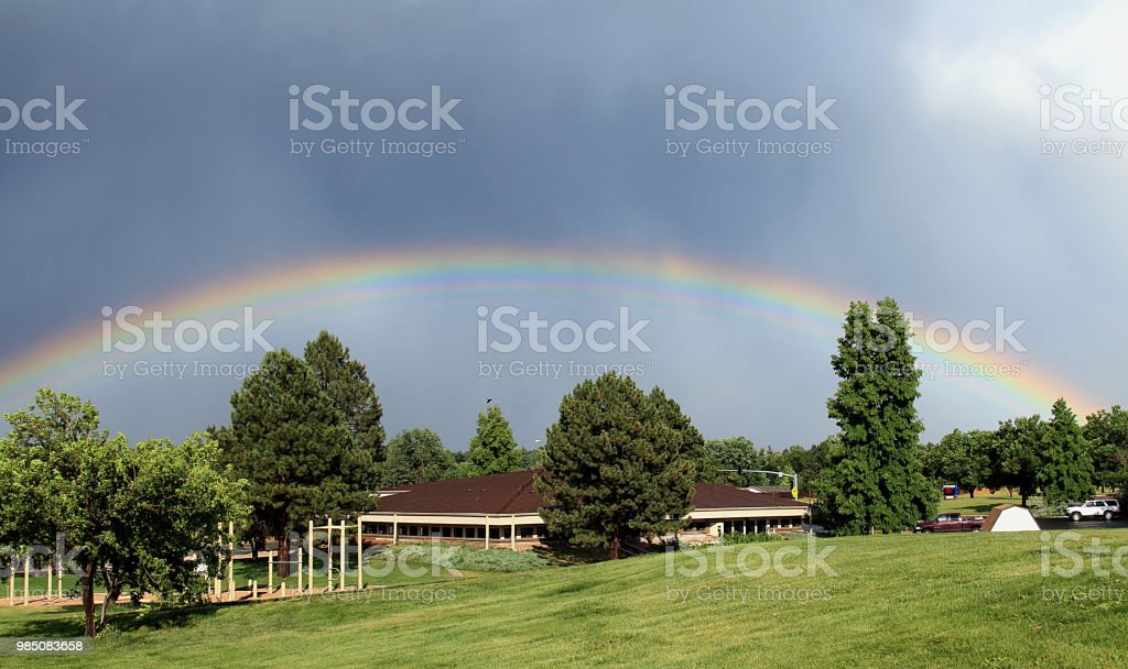Rare and bizarre rainbow over the trees and fair station stock photo
