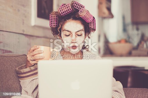 Rare and funny portrait of beautiful woman with facial mask and curlers hair taking a coffee at home while use internet with modern laptop computer - home scene for modern lifestyle people taking his own time