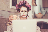 istock Rare and funny portrait of beautiful woman with facial mask and curlers hair taking a coffee at home while use internet with modern laptop computer - home scene for modern lifestyle people taking his own time 1094916486