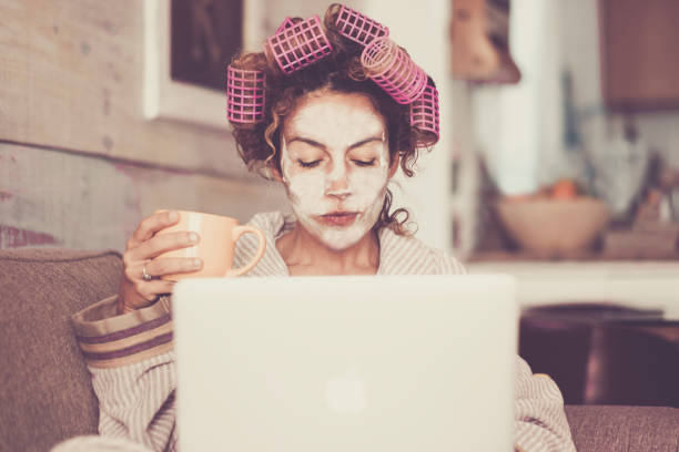 Rare and funny portrait of beautiful woman with facial mask and curlers hair taking a coffee at home while use internet with modern laptop computer - home scene for modern lifestyle people taking his own time stock photo
