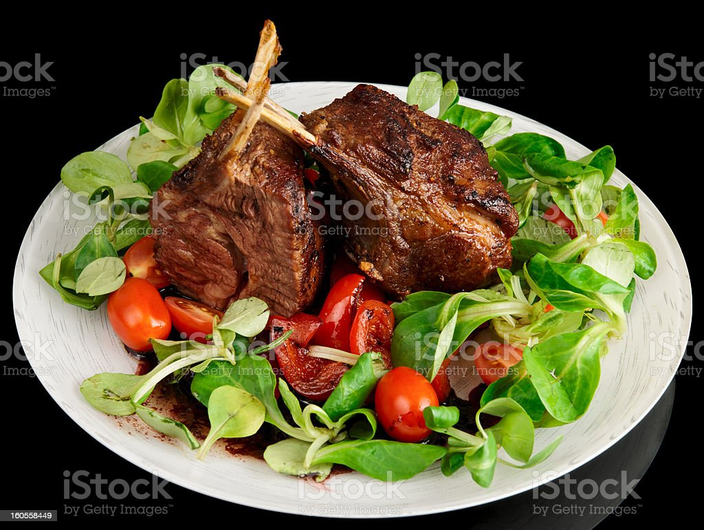Rare fried rack of lamb isolated on black royalty-free stock photo