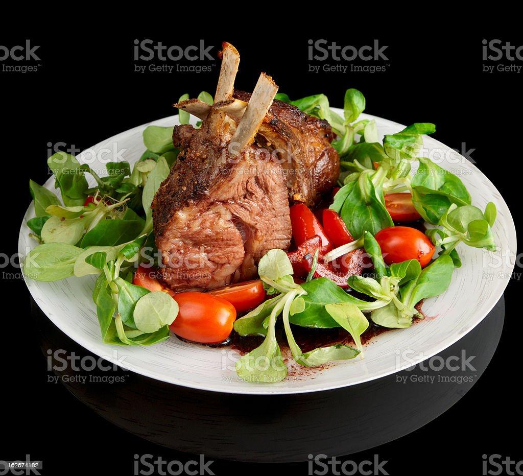 Rare fried rack of lamb isolated on black royalty-free stock photo