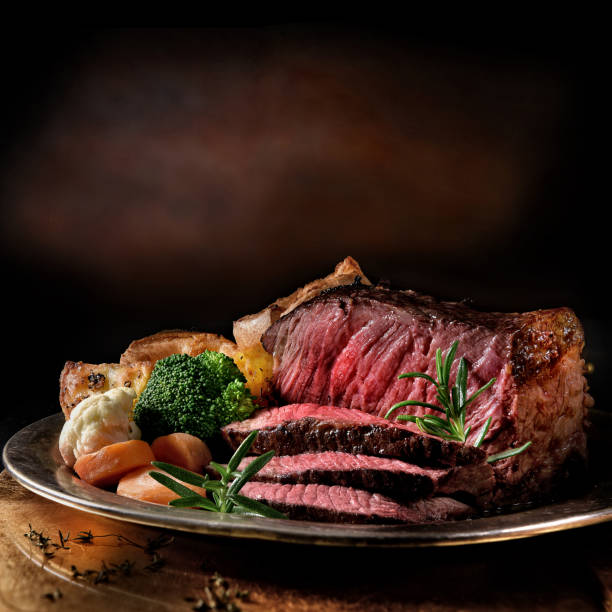 Rare Roast Beef Rare roast beef meal with organic root vegetables and traditional Yorkshire pudding and roast potatoes. Shot against a dark rustic background with generous accommodation for copy space. roast beef stock pictures, royalty-free photos & images
