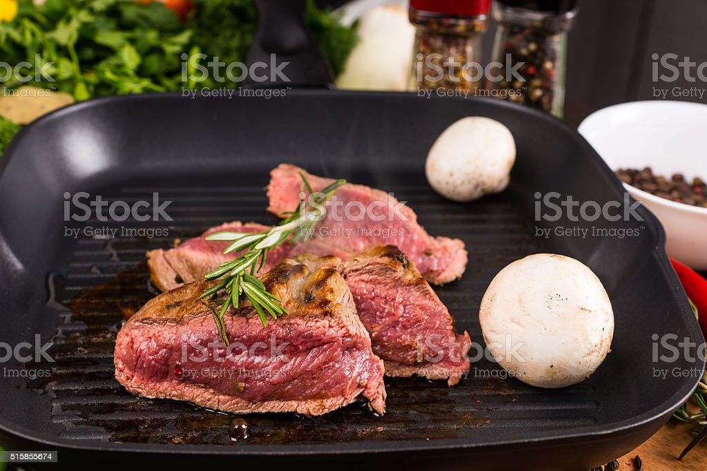 Rare Seasoned Beef Slices Sizzling in Hot Fry Pan stock photo