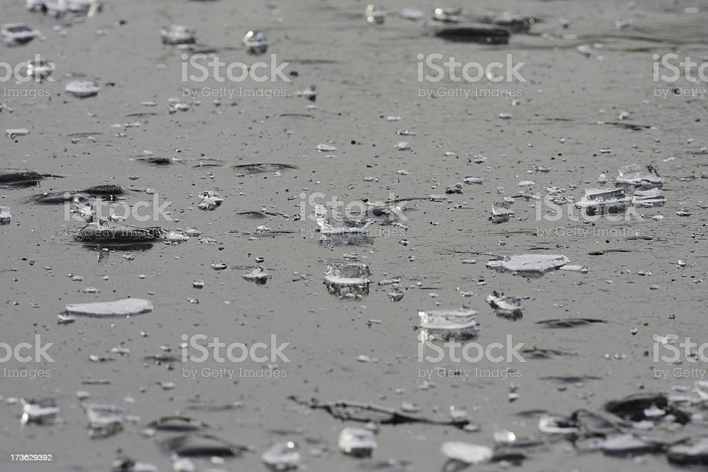 Ice shards scattered over frozen pond surface royalty-free stock photo