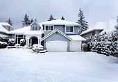 Snow storm in Northwest United States with residential home and dark sky in background