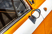 A rarity round small rearview mirror on an orange and white old car in the sun. Horizontal orientation. High quality photo.