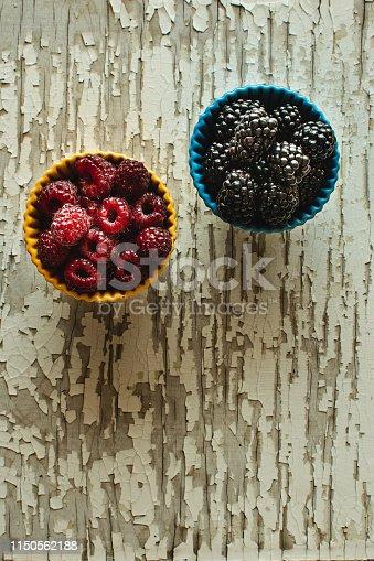 502634476istockphoto Raspberries and Blackberries in Ceramic Bowls on Rustic Wooden Background 1150562188