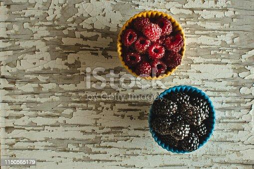 502634476istockphoto Raspberries and Blackberries in Ceramic Bowls on Rustic Wooden Background 1150565179