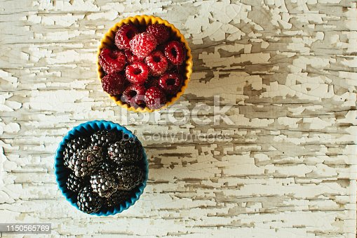 502634476istockphoto Raspberries and Blackberries in Ceramic Bowls on Rustic Wooden Background 1150565769
