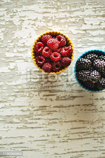502634476istockphoto Raspberries and Blackberries in Ceramic Bowls on Rustic Wooden Background 1150565953