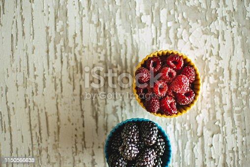 502634476istockphoto Raspberries and Blackberries in Ceramic Bowls on Rustic Wooden Background 1150566638