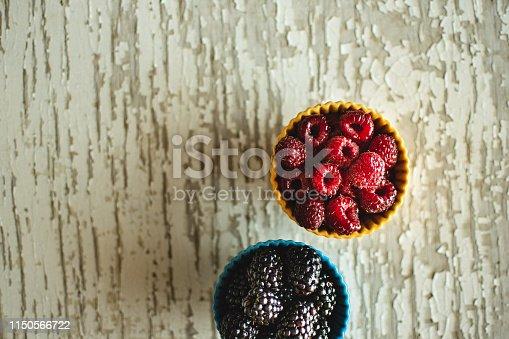 502634476istockphoto Raspberries and Blackberries in Ceramic Bowls on Rustic Wooden Background 1150566722