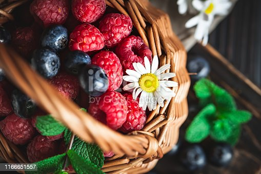 499658564istockphoto Raspberries and blueberries in a basket with chamomile and leaves on a dark background. Summer and healthy food concept. Selective focus. 1166651557