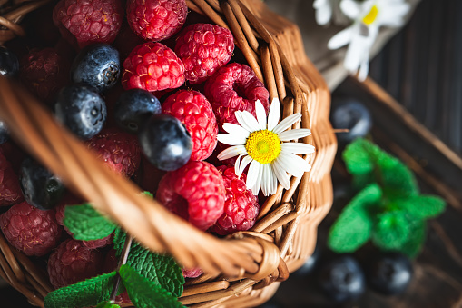 499658564 istock photo Raspberries and blueberries in a basket with chamomile and leaves on a dark background. Summer and healthy food concept. Selective focus. 1166651557