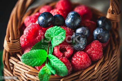 499658564istockphoto Raspberries and blueberries in a basket with chamomile and leaves on a dark background. Summer and healthy food concept. Selective focus. 1166651792