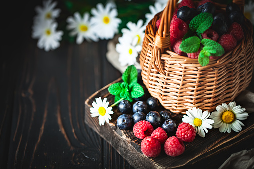 499658564 istock photo Raspberries and blueberries in a basket with chamomile and leaves on a dark background. Summer and healthy food concept. Background with copy space. Selective focus. 1216398703