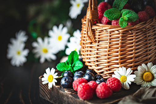 499658564 istock photo Raspberries and blueberries in a basket with chamomile and leaves on a dark background. Summer and healthy food concept. Selective focus. 1220089013