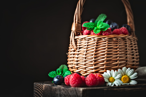 499658564 istock photo Raspberries and blueberries in a basket with chamomile and leaves on a dark background. Summer and healthy food concept. Background with copy space. Selective focus. 1223016526