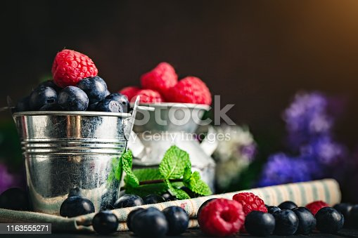 499658564istockphoto Raspberries and blueberries in a Cup on a dark background. Summer and healthy food concept. Background with copy space. Selective focus. Horizontal. 1163555271