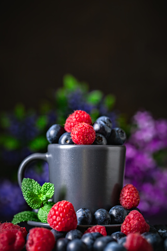 499658564 istock photo Raspberries and blueberries in a Cup on a dark background. Summer and healthy food concept. Background with copy space. Selective focus. Vertical. 1163557366