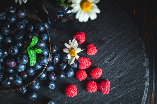 499658564 istock photo Raspberries and blueberries with chamomile and leaves on a dark background. Summer and healthy food concept. Selective focus. 1159397730