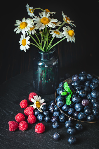 499658564 istock photo Raspberries and blueberries with chamomile and leaves on a dark background. Summer and healthy food concept. Background with copy space. Vertical. 1223014173
