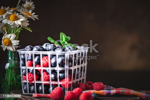 499658564istockphoto Raspberries and blueberry in a basket on a dark background. Summer and healthy food concept. Background with copy space. Selective focus. 1158443689