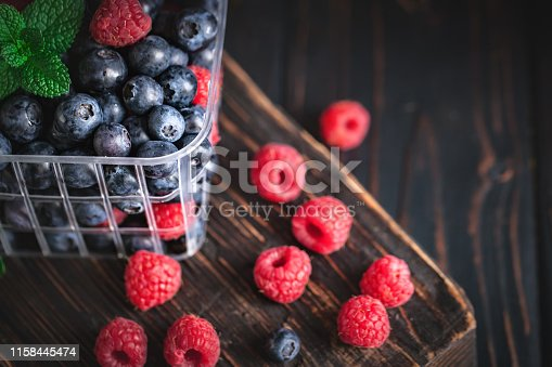 499658564istockphoto Raspberries and blueberry in a basket on a dark background. Summer and healthy food concept. Background with copy space. Selective focus. 1158445474