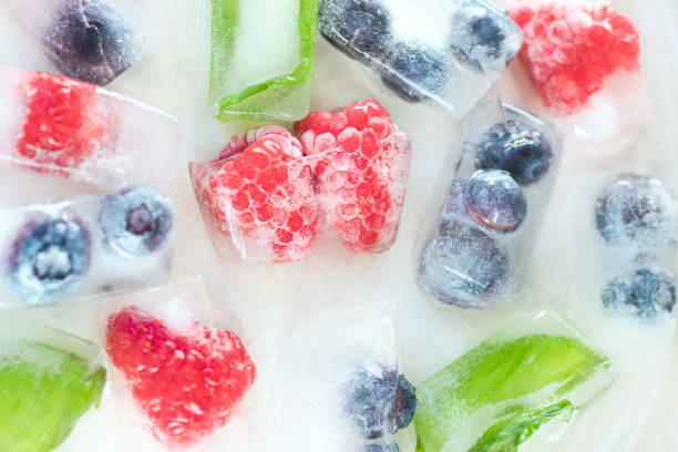 raspberries, blueberries and mint leaves in ice cubes on a white background - frozen berries stock photos and pictures