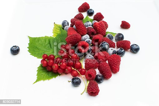 istock Raspberries, blueberries,currants, leaves on white 825032714