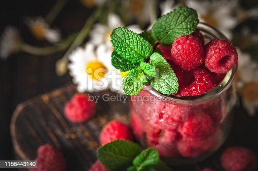 499658564istockphoto Raspberries in a Cup on a dark background. Summer and healthy food concept. Selective focus. Vertical. 1158443140