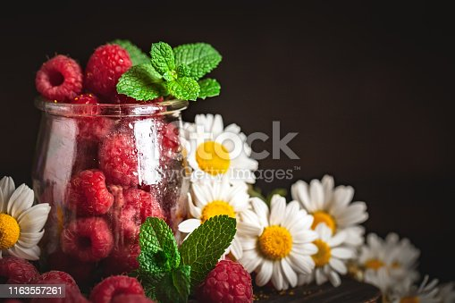 499658564istockphoto Raspberries in a Cup on a dark background. Summer and healthy food concept. Background with copy space. Selective focus. Vertical. 1163557261
