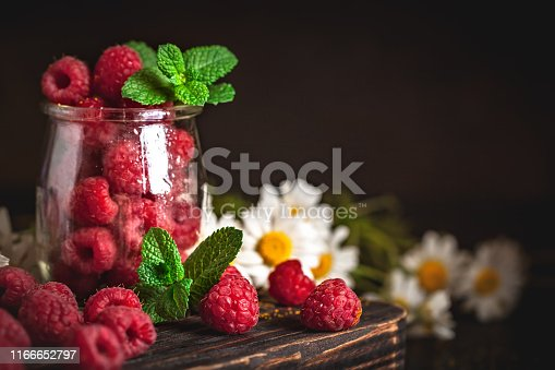 499658564istockphoto Raspberries in a Cup on a dark background. Summer and healthy food concept. Background with copy space. Selective focus. Vertical. 1166652797
