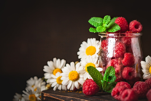 499658564 istock photo Raspberries in a Cup on a dark background. Summer and healthy food concept. Background with copy space. Selective focus. Vertical. 1220086888