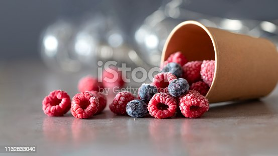 Frozen raspberry and blueberry berries fell out of a disposable cup on gray background.