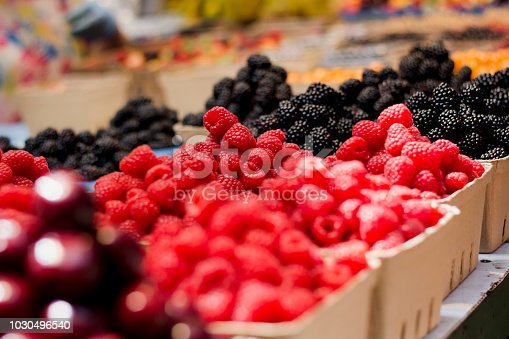 Raspberries and other produce on display in a market.