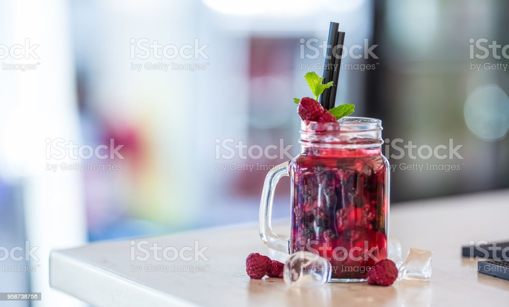 Raspberries non alcoholic lemonade with mint leaves and ice cubes stock photo