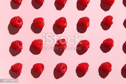 Arranged raspberries on a pale pink yoghurt background