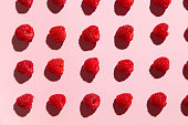 Arranged raspberries on a pale pink yoghurt background