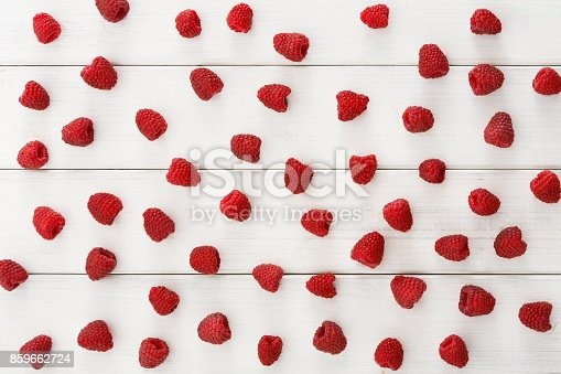 862604802 istock photo Raspberries on white wooden table top view 859662724