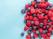 Background of raspberries and blueberries. Raspberry and blueberry on blue background with copy space. Summer and healthy food concept, Top view or flat lay.