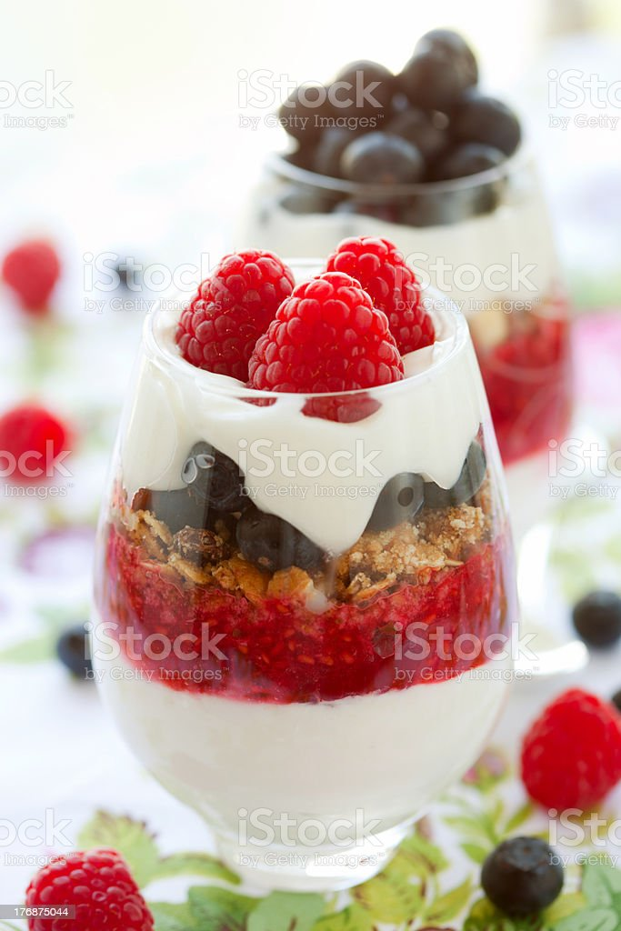 Raspberry and blueberry parfaits in glasses stock photo