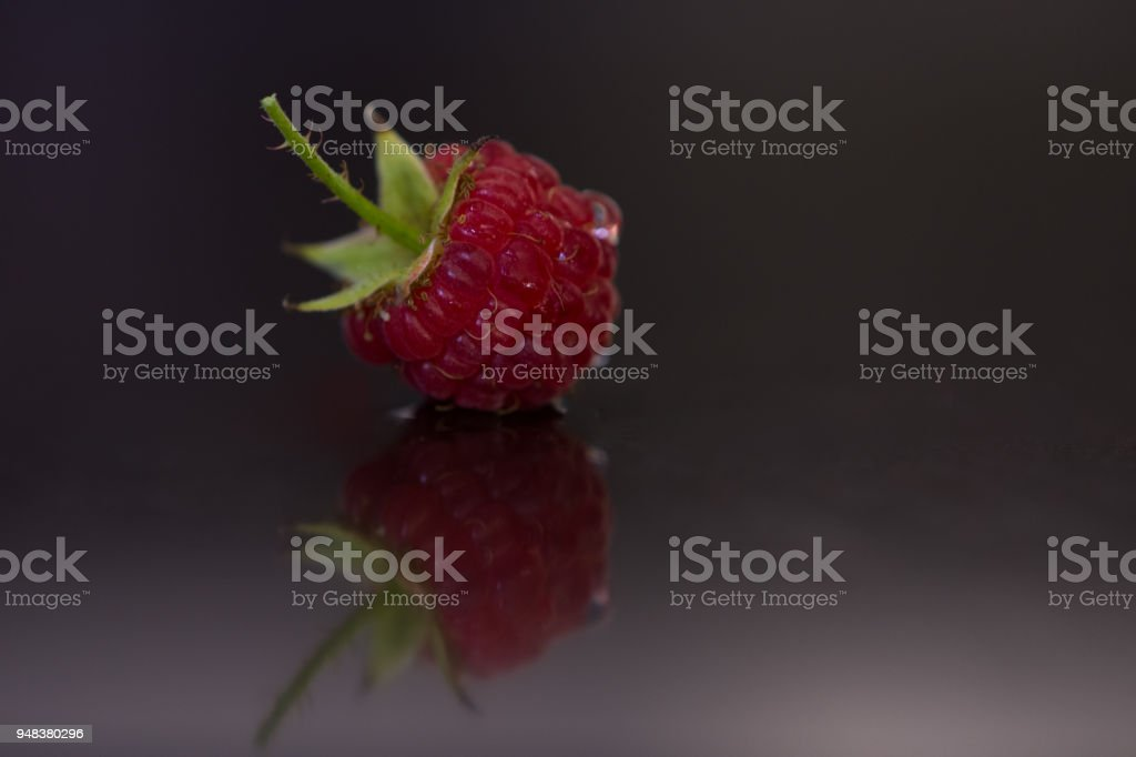A Raspberry Close Up Against a Dark Brown Counter Top stock photo