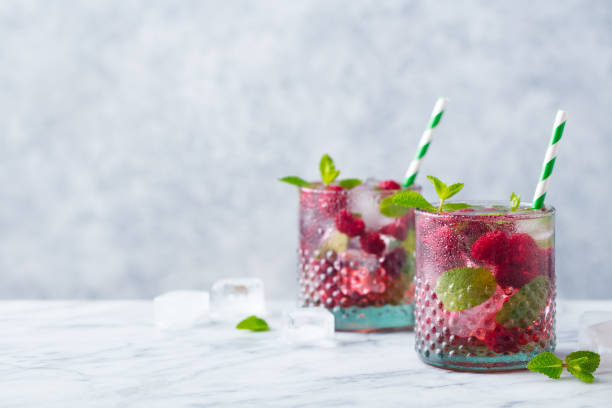 Raspberry cocktail, fizz, lemonade, ice tea with fresh mint on marble background. Copy space. stock photo