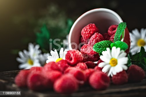 499658564istockphoto Raspberry in a red cup with chamomile and leaves on a dark background. Summer and healthy food concept. Background with copy space. Selective focus. 1156900153
